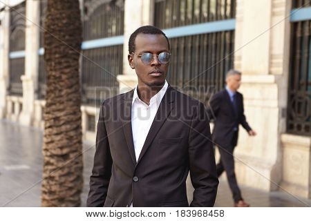 Outdoor Portrait Of Handsome Serious Young Black European Businessman Wearing Round Sunglasses And B