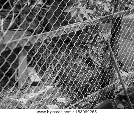 BLACK AND WHITE PHOTO OF CHAIN-LINK FENCE (ALSO REFERRED TO AS WIRE NETTING, WIRE-MESH FENCE, CHAIN-WIRE FENCE, CYCLONE FENCE, HURRICANE FENCE, OR DIAMOND-MESH FENCE)