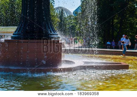 YEKATERINBURG RUSSIA - AUGUST 24 2013. Park summer view - splashing fountain in the city arboretum exhibition and a lot of people having fun in summer sunny day in Yekaterinburg Russia