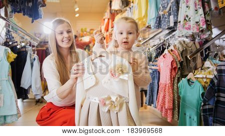 Blonde young woman with little daughter buying kids dress in clothes store, telephoto