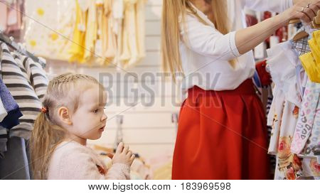 Daughter with mother buying kids clothes in store, telephoto