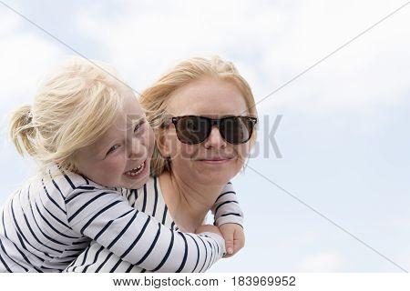 Little Girl Piggy Backing On Mother