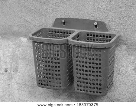 BLACK AND WHITE PHOTO OF PLASTIC BASKET SCREWED ON CONCRETE WALL
