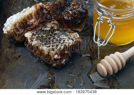Honey Background. Natural Honey Comb And A Glass Jar. On Black Rustic Table
