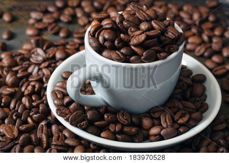 Coffee beans in coffee cup dark mood