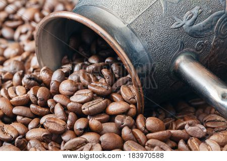 brass coffee pot lay on roasted beans