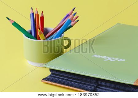 Photo album book on plain yellow background