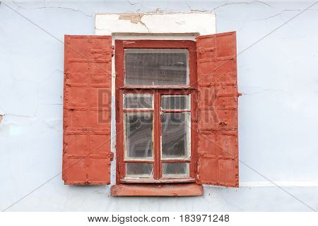 Old wooden window with metal shutters close up