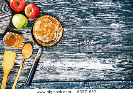 Apple pancakes with cinnamon and honey on textured wood boards. Fresh apples and wooden tableware. Copy space. Top view