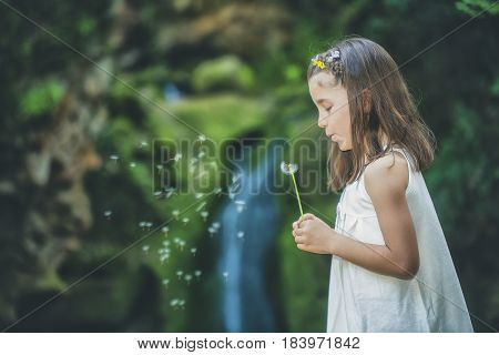 Little girl plays with flowers by a river