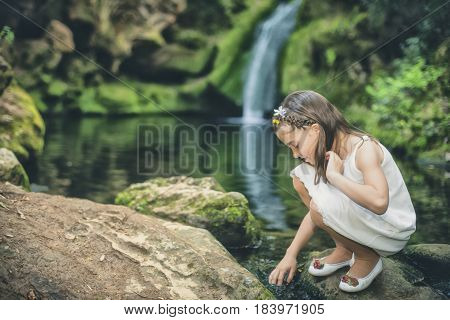 Little girl plays sweetly with water beside the bed of a river