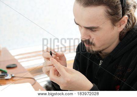 sculptor artist man making handmade miniature plastic toy house decoration craftsmanship hobby decor creation process
