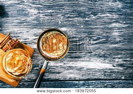 Apple pancakes with cinnamon and honey on textured wood boards. Copy space. Top view