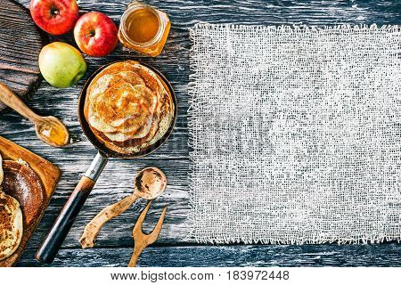 Apple pancakes with cinnamon and honey on textured wood boards. Fresh apples and wooden tableware. Burlap frames. Top view