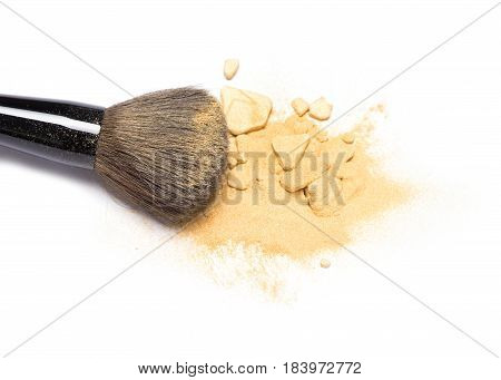 Close-up of makeup brush with crushed mineral shimmer powder golden color on white background
