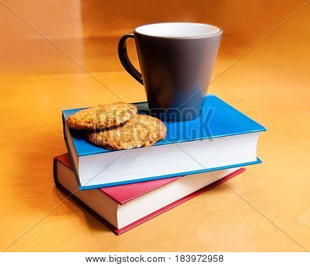 Cup of  tea with cookies and books