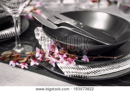 Tree branch with flowers on served table, closeup