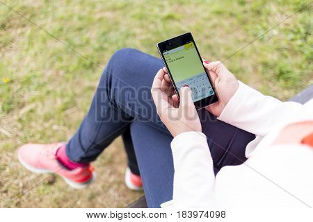 Young Woman Working With Smartphone In The Park