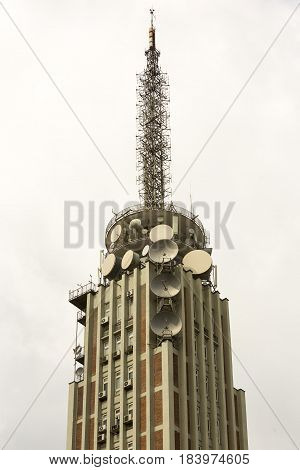 Old television broadcast tower with satellite dishes and communication antennas.