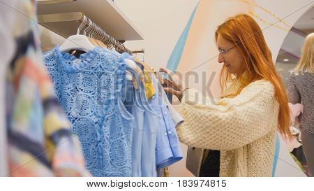 Attractive girl in a fashion dress store chose a clothe - fashion shopping, close up