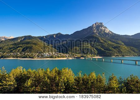 Savines-le-Lac the Grand Morgon peak and Serre-Poncon lake in summer. Late afternoon light on the Savines bridge Hautes-Alpes Southern French Alps France