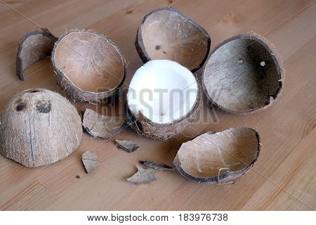 Still life with broken coconut shell ripe white flesh inside and debris on brown wooden table as background. Horizontal close up photo