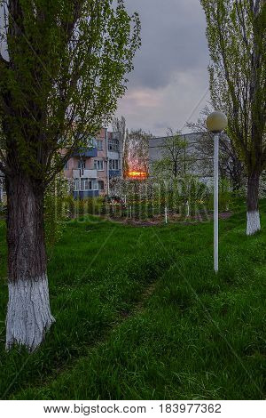 Three-storey house in the village of Uspenskoye, Krasnodar Krai, in the gaps between them see the sunrise, and the grass, trees, flowers.The General background is dark because it's still early.