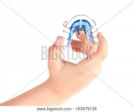 Orthodontic treatment in a child's hand, isolated on a white background