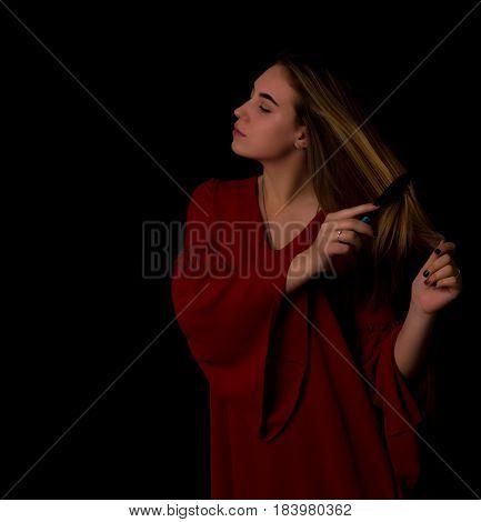 Young pretty woman uses hairbrush, beautiful girl