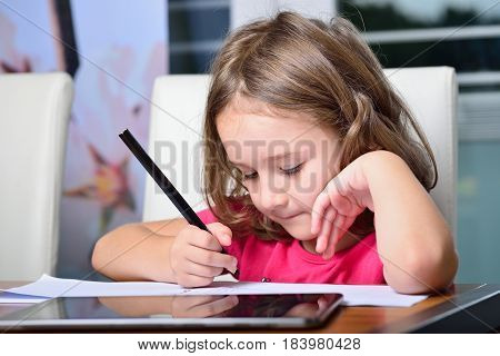 Little cute blonde girl using at home a Tablet PC for homework
