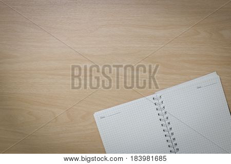 Top view Notebook on the desk is a wooden surface with copy space