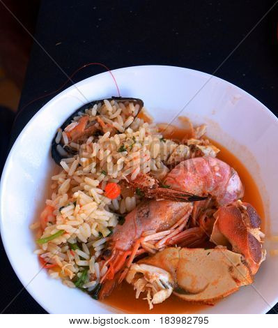 A huge plate of seafood and rice. Very tasty food on a light background.