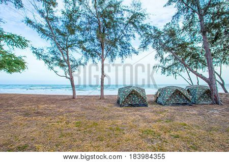 tents on beach of white sandunder blue sky with sweeming people