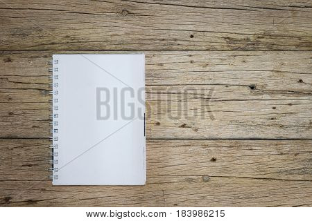 Empty blank notes rest on old wooden floor.