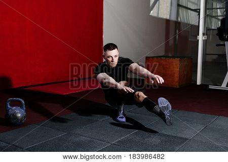 Muscular bearded man doing pistol squats on one leg in gym