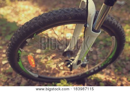 Wheel of a bicycle close-up protector in a forest in spring. Adventures, guided trips in the woods, outdoor park. Healthy lifestyle.