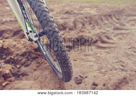 The bike wheel protector treads on the dirty road. Brown mud in the background. Adventures on bicycles. Riding a bicycle outdoors.