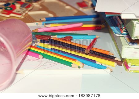 Color pencils and books are scattered on the children's table. The atmosphere of children's art and art. Drawing, crafts, children's imagination.
