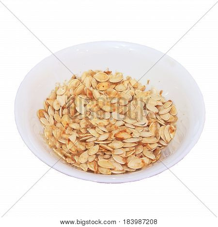 Plate with dried white sunflower seeds isolated on white background. Seeds of zucchini dried in a plate