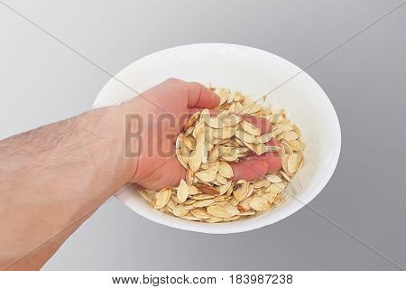 A man's hand takes white sunflower seeds from a plate isolated on a gray background. White dried sunflower seeds.