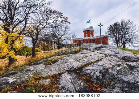Kastellet fortress, small brick citadel located on Kastellholmen island. Autumn Stockholm scene with city public park and famous tower on the rock with swedish flag.