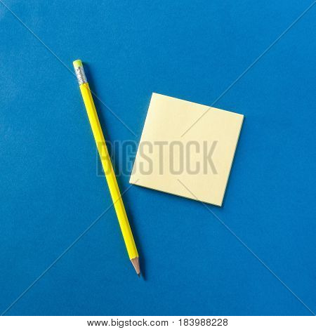 Neon yellow pencil and notepad on blue background, top view
