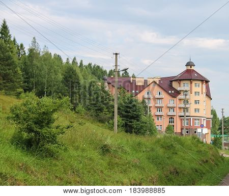 Modern apartment building on of forested mountains. Carpathians Ukraine