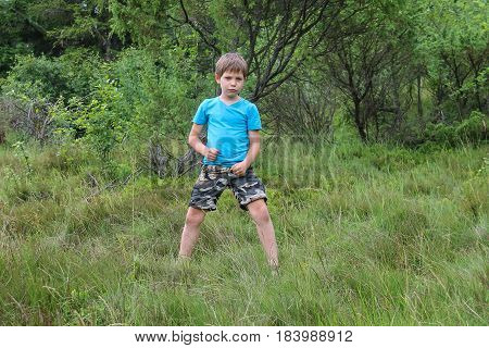 Boy stands among trees in summer forest park