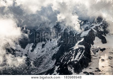 mountain range with glacier covered by clouds