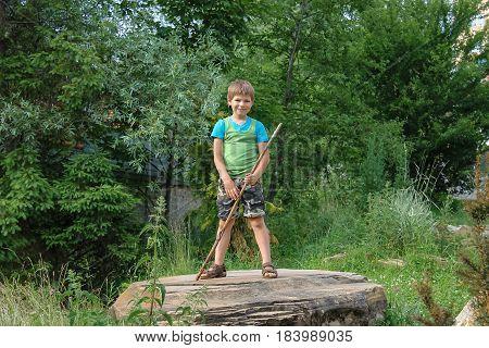 Smiling boy with stick on big stone