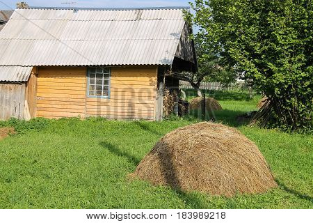 Haystack on green lawn in front of wooden house