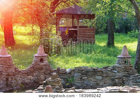 Decorative pond and small wooden pavilion in summer garden in sunlight
