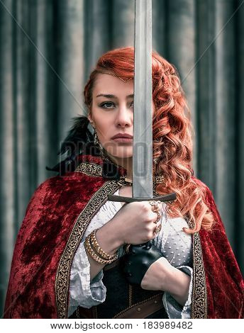 Warrior woman with sword in medieval clothes on the street portrait