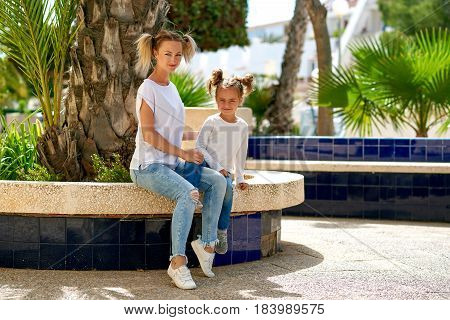 Beautiful mother and daughter sitting on the bench outdoors. Summer photoshoot